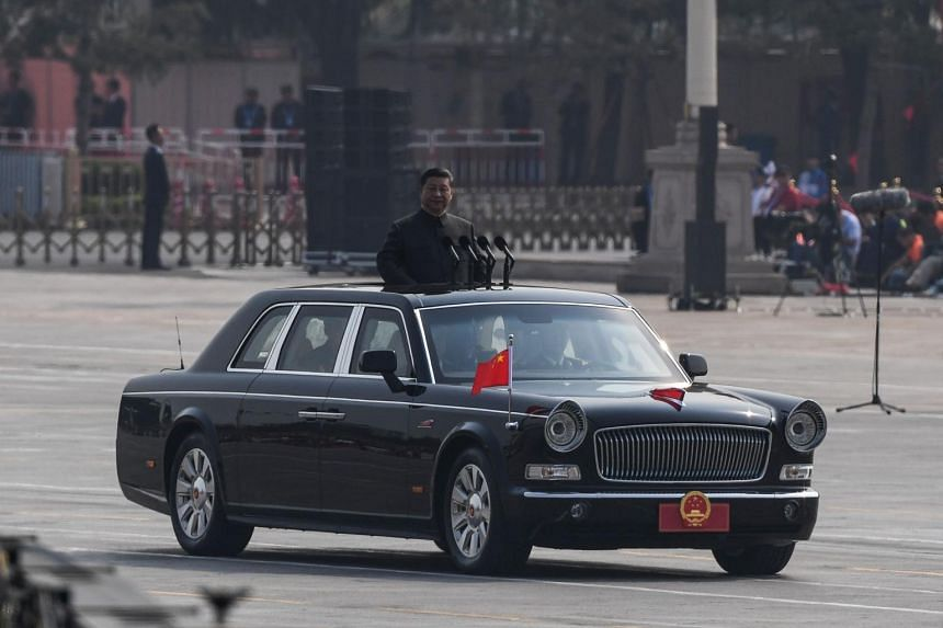 Chinese President Xi Jinping stands in a vehicle as he prepares to review troops at the military parade at Tiananmen Square.