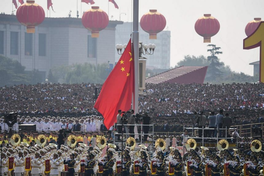 A Chinese national flag being raised during the military parade at Tiananmen Square.