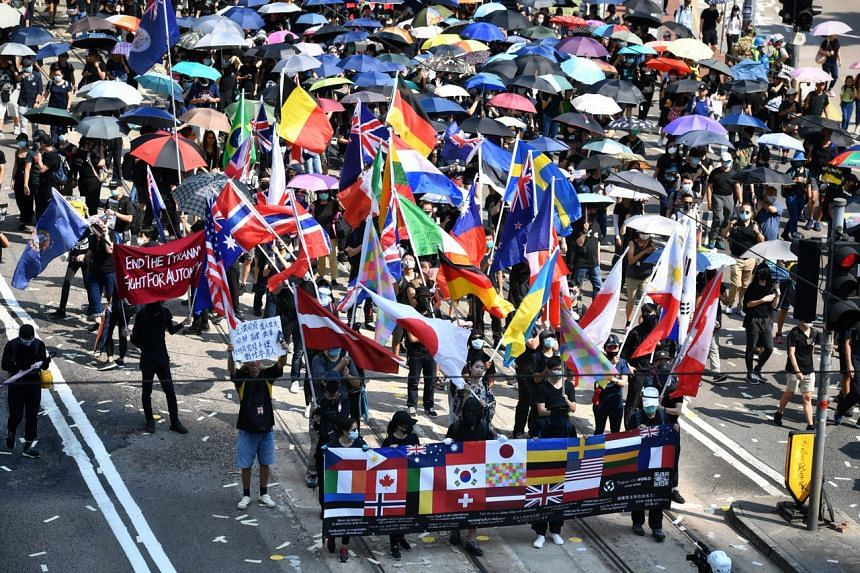 Protesters bearing flags of various nations march past the police HQ in Wan Chai on Oct 1, 2019.