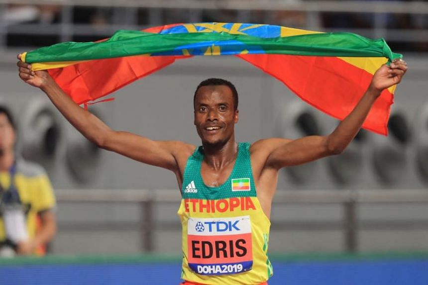 Ethiopia's Muktar Edris celebrates with the national flag after winning the Men's 5000m final at the 2019 IAAF Athletics World Championships at the Khalifa International Stadium in Doha on Sept 30, 2019.
