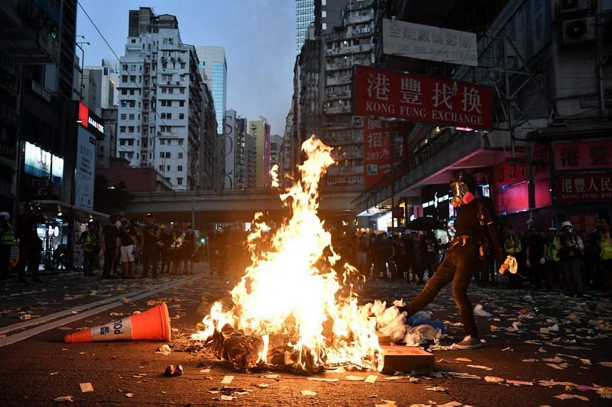 A protester starts a fire in a bid to slow down police advancement in Hong Kong's Wan Chai district on Oct 1, 2019.