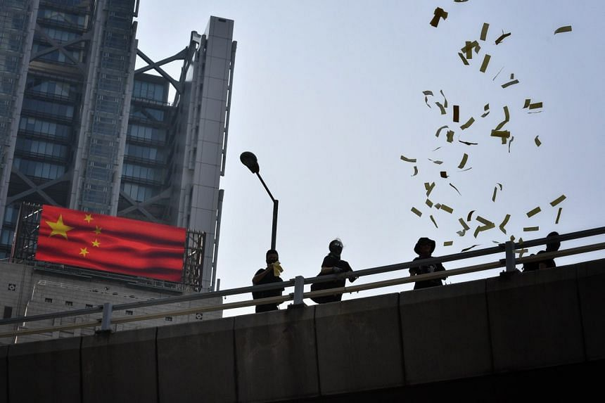 """Protesters toss paper offerings, as a way to """"mourn"""" China's 70th National Day, in Hong Kong on Oct 2, 2019."""
