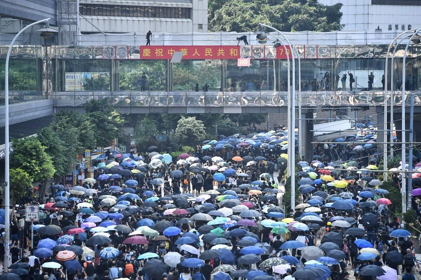 Protesters tearing off decorations for China's 70th National Day on an overhead bridge in Admiralty on Oct 1, 2019.