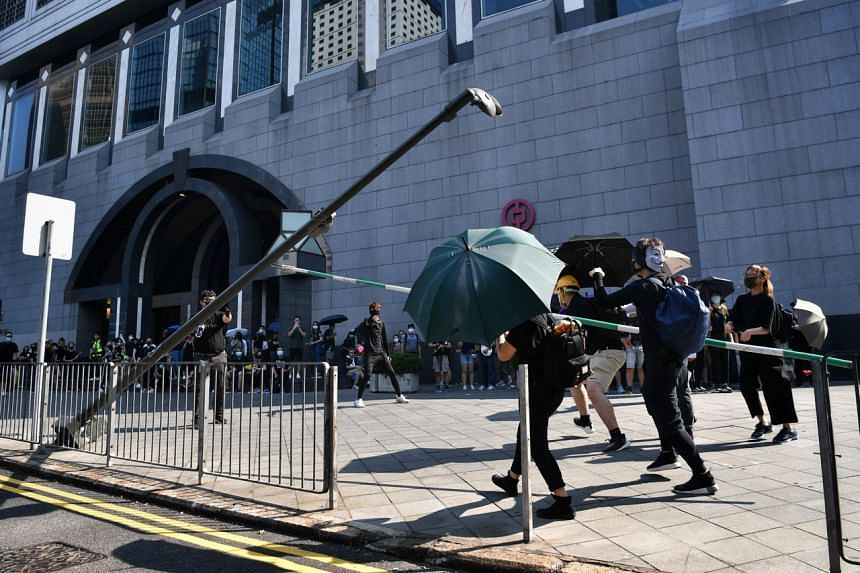 Protesters bring down a lamp post with a surveillance camera outside the Bank Of China Tower in Hong Kong on Oct 1, 2019.