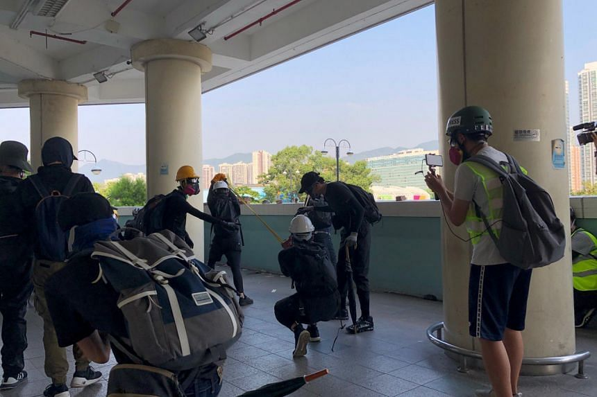 Protesters using a catapult to toss bricks and eggs at riot police from the second level of Lucky Plaza in Sha Tin on Oct 1, 2019.