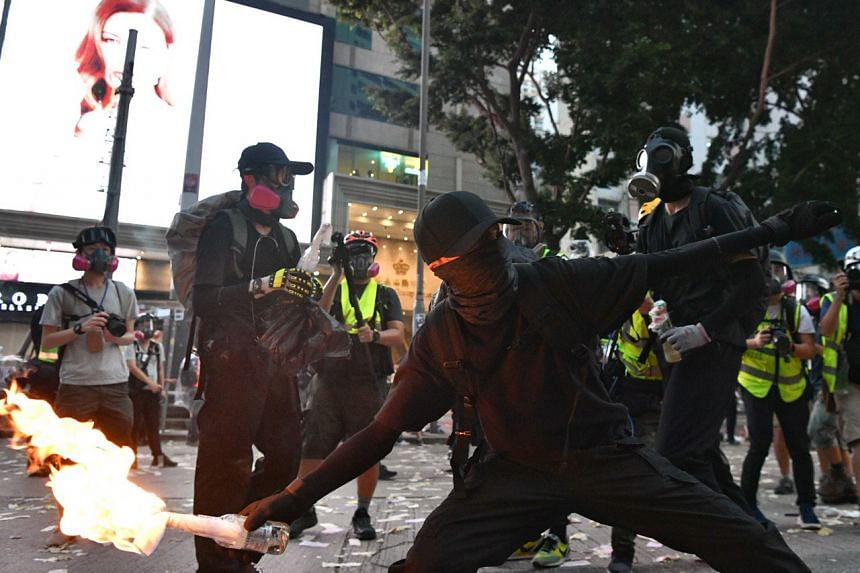 Protesters take turns to throw petrol bombs at the police in a bid to slow down their advancement in Hong Kong's Wan Chai district on Oct 1, 2019.