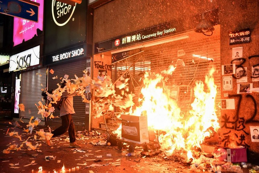 """A protester burns the exit of Causeway Bay MTR station with paper offerings as he shouts """"China, come receive your present"""" on Oct 1, 2019."""