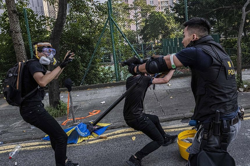 Police and protesters clashing in Hong Kong yesterday. PHOTO: NYTIMES Above: A photo received from Hong Kong police showing an officer who was injured after a corrosive substance was allegedly thrown by protesters in the Tuen Mun area yesterday. PHOT