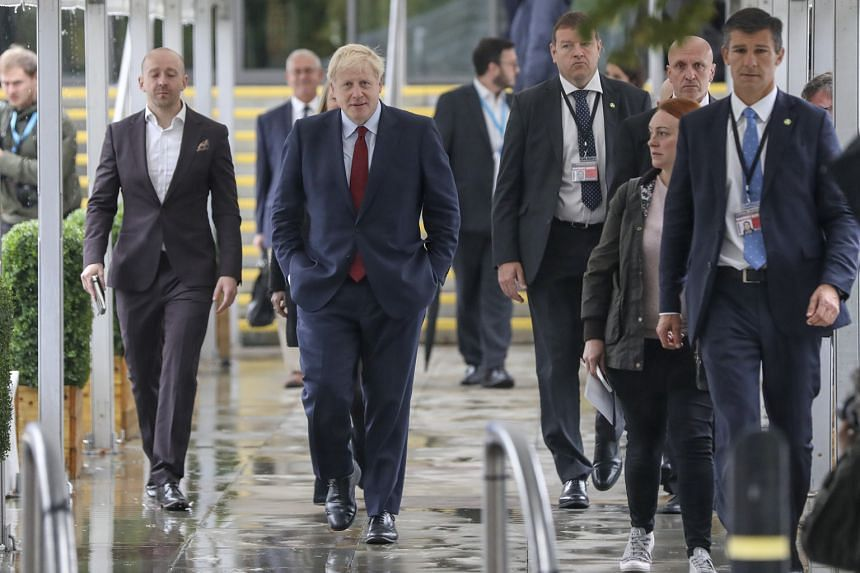 British Prime Minister Boris Johnson (centre) heading for the Conservative Party conference in Manchester yesterday. He appears to be no nearer to finding a formula to separate Britain from the EU without risking further political and economic chaos.
