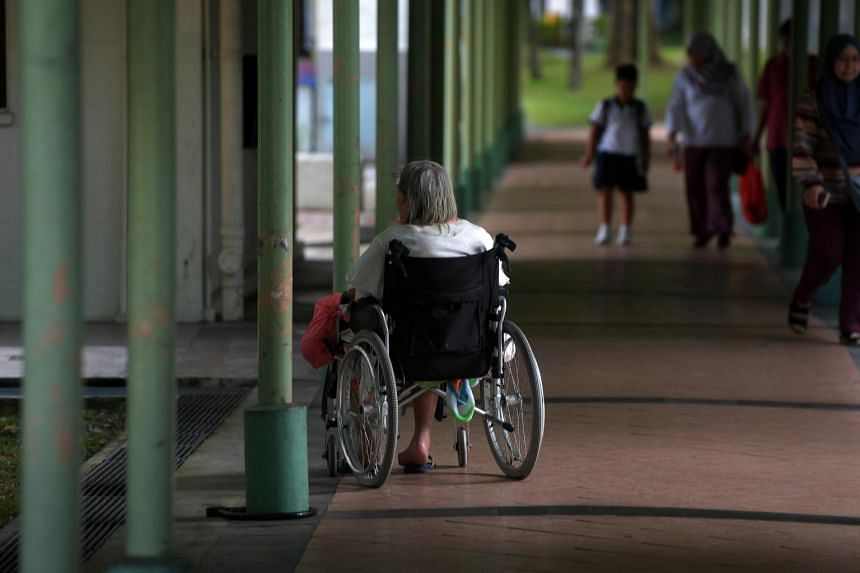 An elderly woman on a wheelchair along a covered walkway in Toa Payoh.