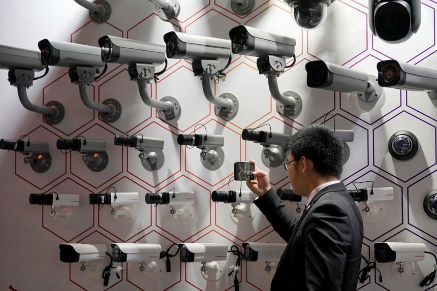 In a photo from Sept 18, 2019, a man looks at surveillance cameras at the annual Huawei Connect event in Shanghai. A universal approach to safeguard connected devices - collectively known as the Internet of Things (IoT) - is wanting.