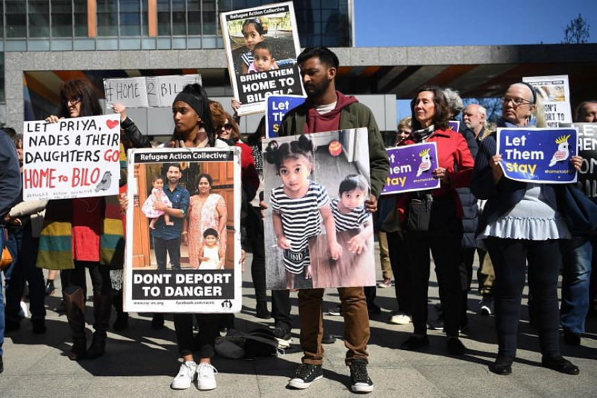 Protesters holds up placards in Melbourne on Sept 1, 2019, during a rally in support of a Tamil asylum seeker family. They have been held at the Christmas Island detention facility for the past month.