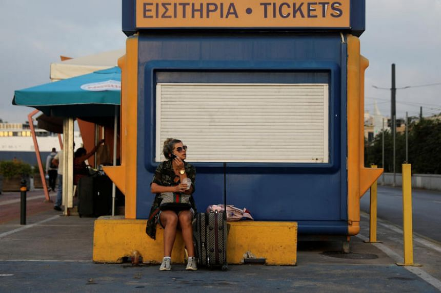 A passenger sits next to a closed ticket booth during a 24-hour walkout at the port of Piraeus, Greece, on Oct 2, 2019.