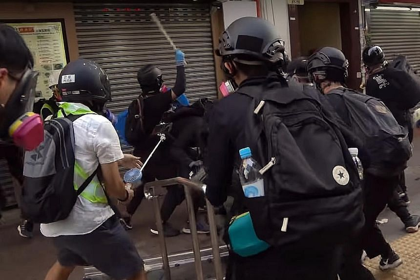 Screenshots from a video showing the sequence of events during clashes in Tsuen Wan, Hong Kong, on Tuesday. From top: The 18-year-old protester dressed in black (centre, holding up pole) attacks a police officer. Another officer then shoots the teena