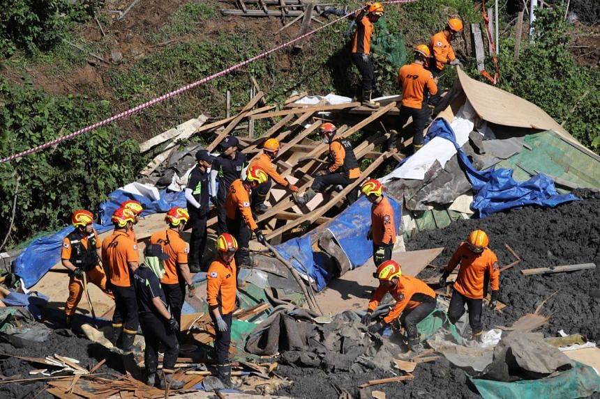 South Korea's firefighters search for missing people in an area struck by a landslide in the aftermath of Typhoon Mitag, in Busan, South Korea on Oct 3, 2019.