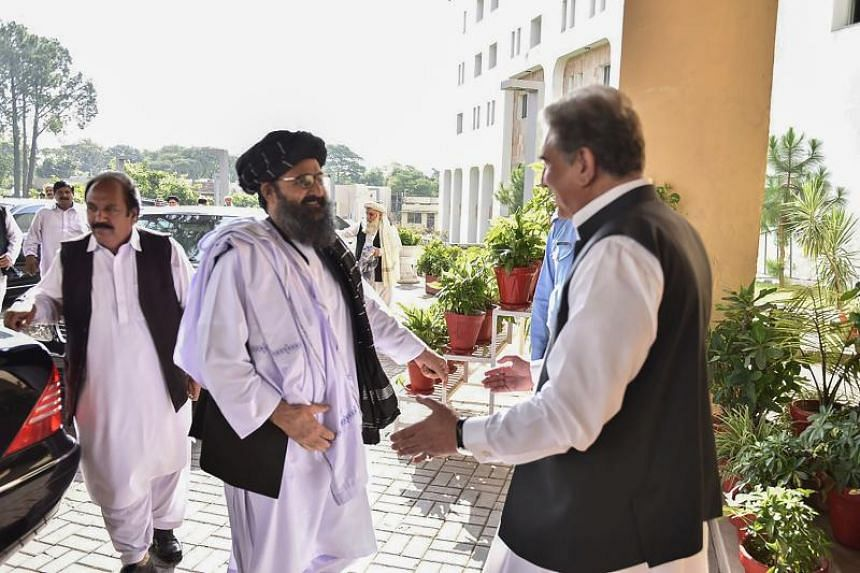 Pakistan's Foreign Minister Shah Mehmood Qureshi (right) greets Taleban co-founder Mullah Baradar upon his arrival with his delegation at the Pakistan Foreign Ministry in Islamabad on Oct 3, 2019.