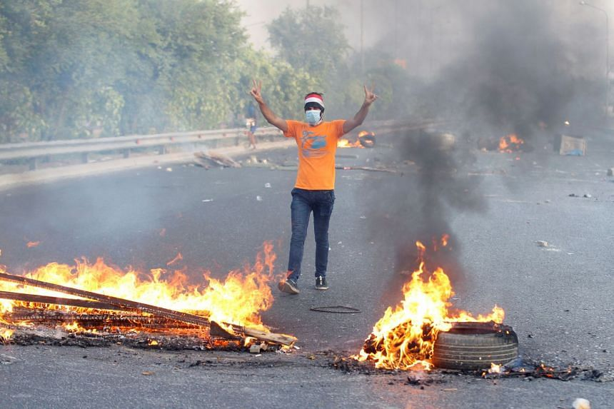A demonstrator gestures near burning objects on the road in Baghdad, Oct 3, 2019.