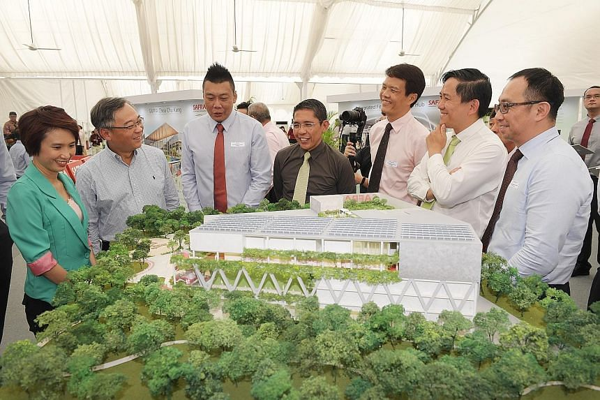 (From left) Senior Parliamentary Secretary for Manpower and Education Low Yen Ling and Health Minister Gan Kim Yong, both MPs for Chua Chu Kang GRC, looking at a model of the Safra Choa Chu Kang clubhouse yesterday, along with the clubhouse's develop