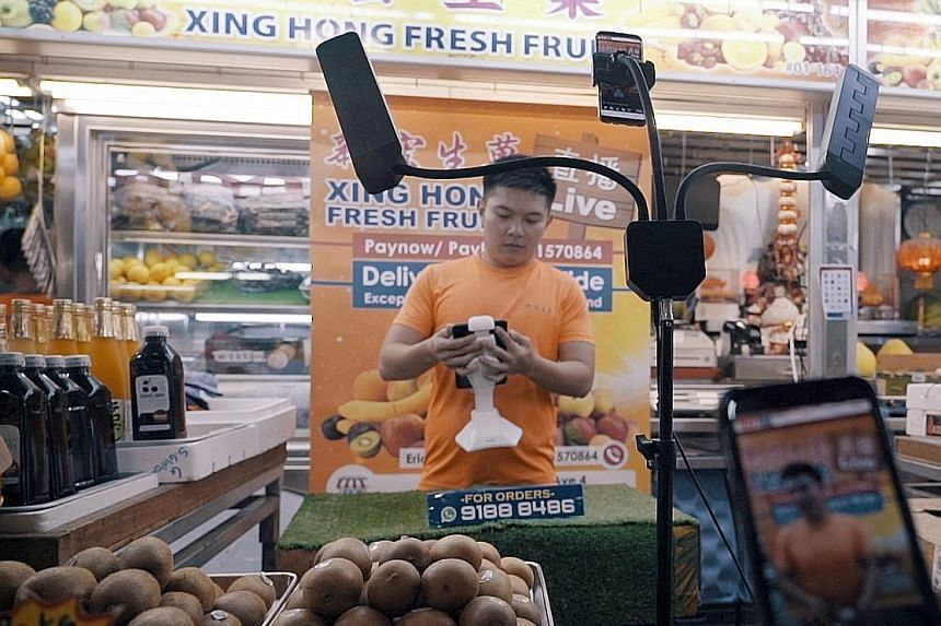 Fruit seller Eric Ang with the Facebook live-streaming set-up at his stall in Ang Mo Kio Market and Food Centre, which he uses to hawk his produce for a few hours at a time a couple of days a week.