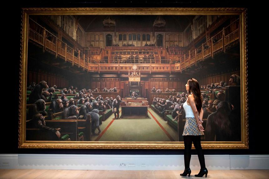 A gallery assistant poses with an artwork entitled Devolved Parliament by British artist Banksy.