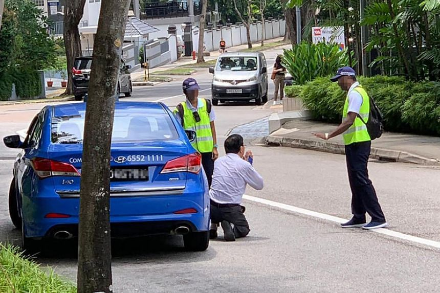 In a widely circulated photo, the male taxi driver is seen on his knees in Mount Elizabeth Road begging two officers wearing Certis caps, on Oct 3.