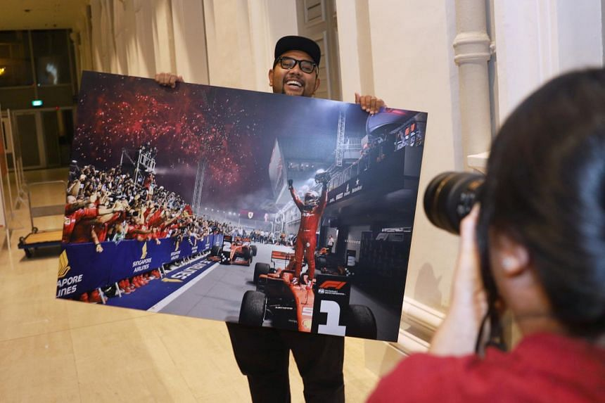 Straits Times photographer Ariffin Jamar holds a photo he took of Ferrari's Sebastian Vettel celebrating after winning a record fifth title at the Singapore Airlines Singapore Grand Prix on Sept 22, 2019.