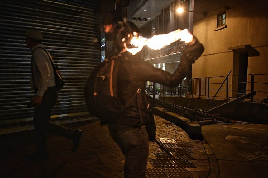 A protester throws a petrol bomb to light up a makeshift blockade in Hong Kong's Wan Chai district on Oct 4, 2019.