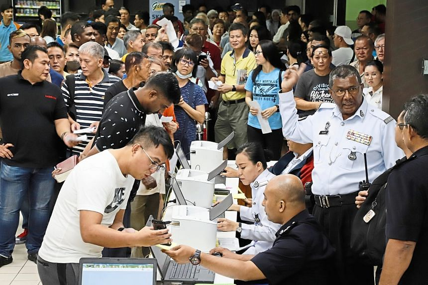 Motorists stand in line to verify outstanding traffic summonses with police officers in Penang, Malaysia on Oct 4, 2019.
