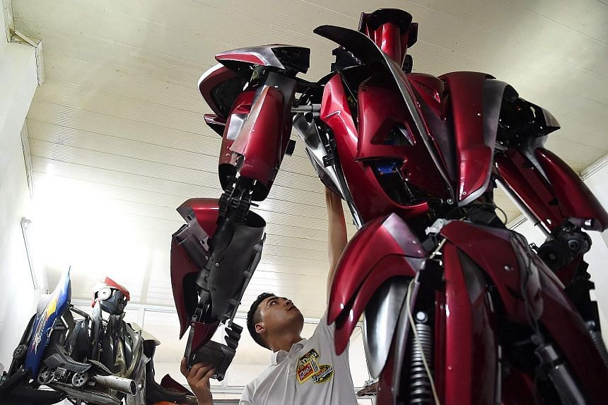 Vietnamese engineer Do Danh Phong working on the 3m-tall Robot One, which is cobbled together from the remnants of Japanese Honda and Taiwanese SYM motorbikes, at a workshop in Hanoi earlier this week. Its creators say they want to provoke debate abo