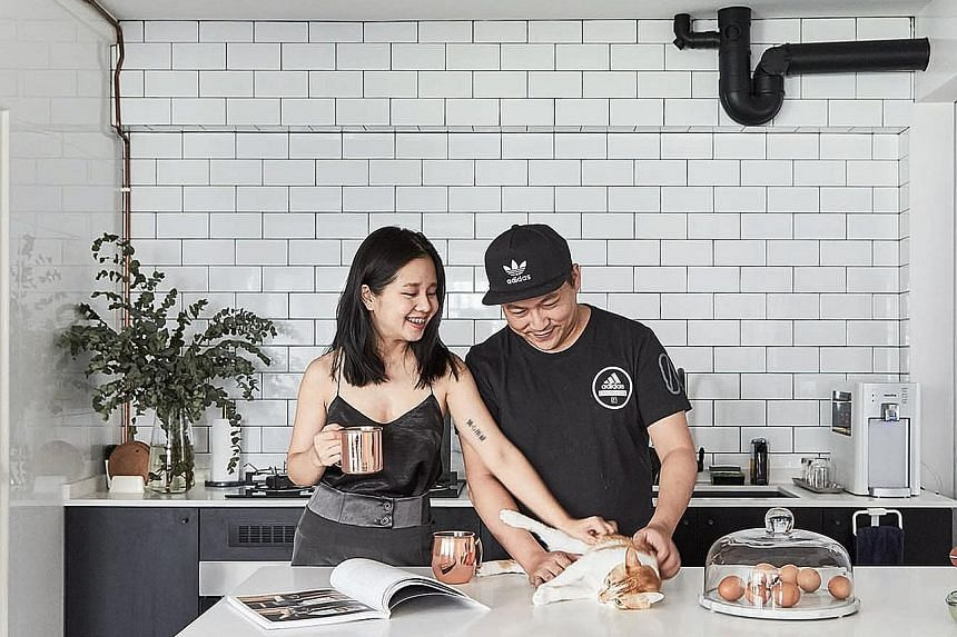 The wall separating the living room and kitchen in the home of Ms Rachel Ong and Mr Ronald Wan (both above) was replaced by a bar counter to open up the spaces.