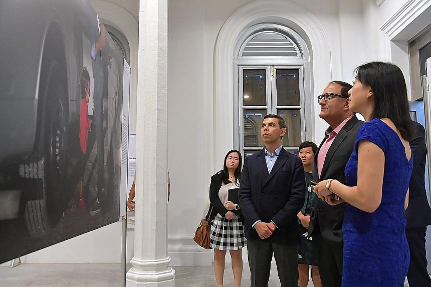 Above: Minister for Communications and Information S. Iswaran (second from right), flanked by Straits Times editor Warren Fernandez and World Press Photo curator Yi Wen Hsia, viewing the World Press Photo of the Year, taken by Getty Images senior sta