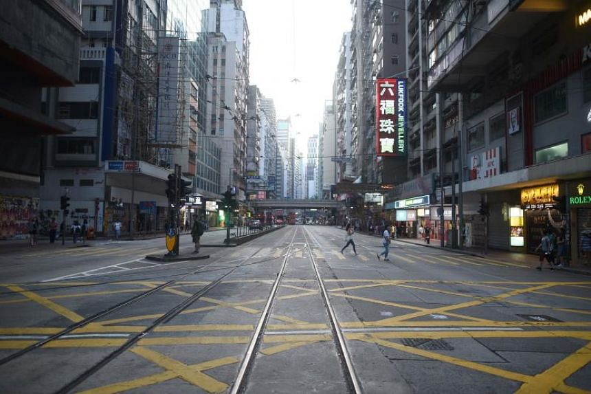A usually busy road in Hong Kong's Causeway Bay shopping district is pictured mostly empty of people and traffic in the afternoon on Oct 5, 2019.