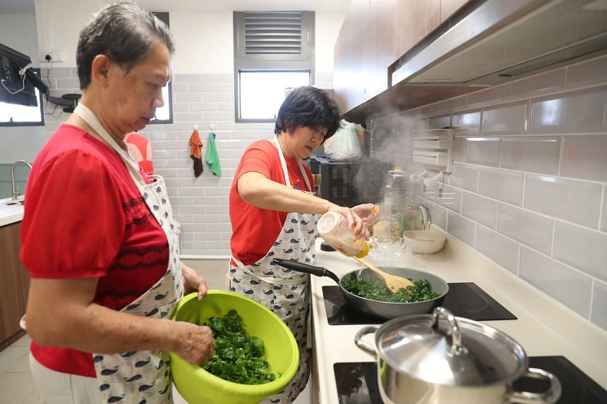 Volunteers cooking at Kampung Admiralty's active ageing hub. Run by NTUC Health, the hub waives membership fees for participants who volunteer at least three hours a week.