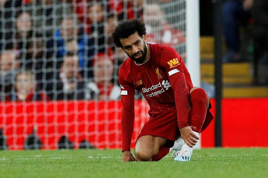 Liverpool's Mohamed Salah reacts after sustaining an injury.