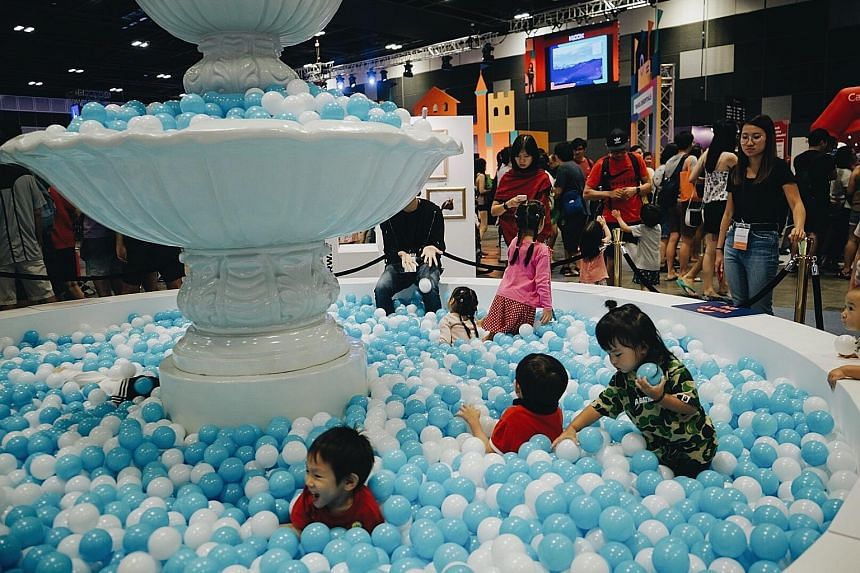 Children playing in a mini replica of Rome's Trevi Fountain during Klook's inaugural travel fair at Suntec convention centre yesterday. Besides access to exclusive Klook promotional codes, visitors can also look forward to flash deals, such as one-fo