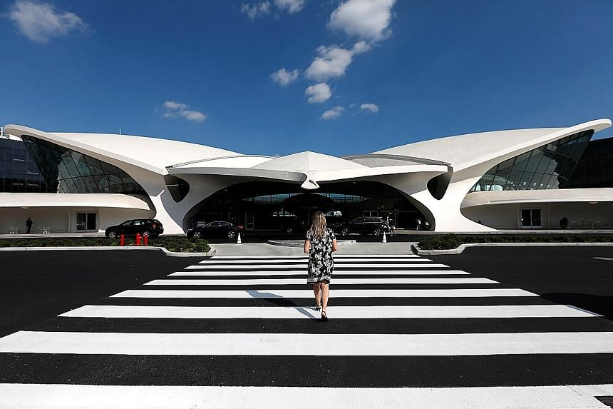 A traveller approaches the TWA Hotel inside New York's John F. Kennedy International Airport. The recently opened hotel was once Trans World Airlines' terminal. It was built in 1962 as an uplifting symbol of the Jet Age and was designed by renowned F