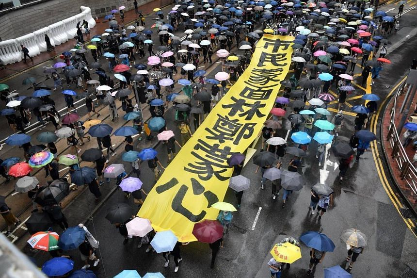 """Protesters in Wan Chai marching while carrying a banner reading """"Citizens mask their face, Carrie Lam masks her heart"""", on Oct 6, 2019."""