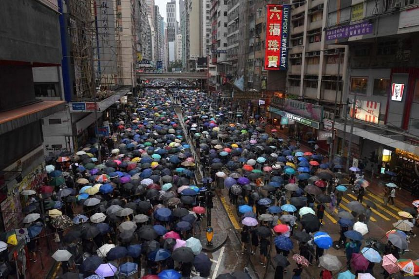 People taking part in a protest march during a rainy day at the Causeway Bay shopping district of Hong Kong, on Oct 6, 2019.