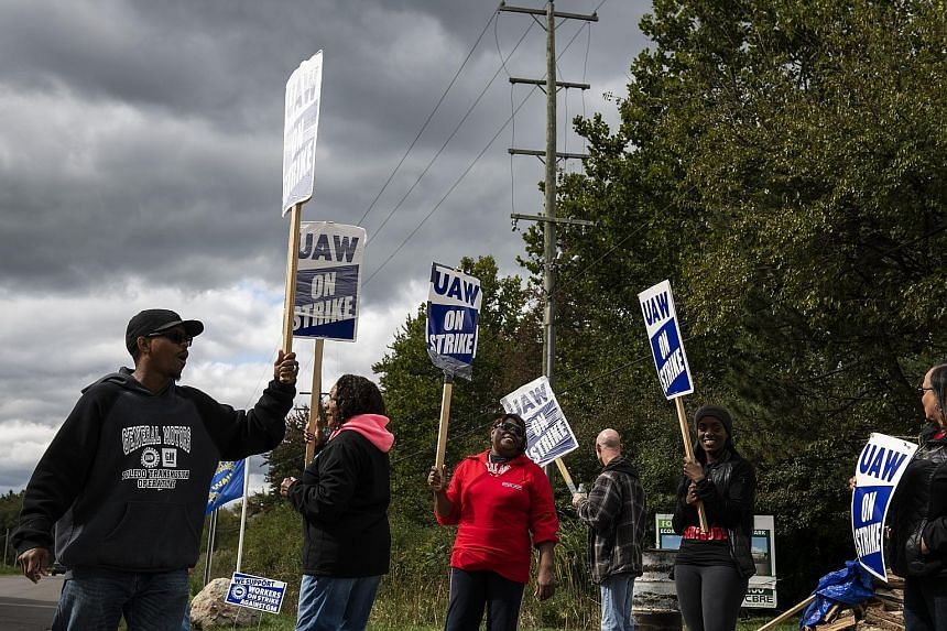 Demonstrators holding signs and shouting slogans during a United Auto Workers strike outside the General Motors plant in Romulus in America's Michigan state last Friday.