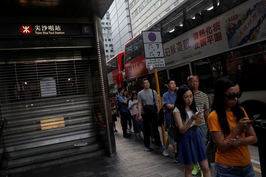 People queue as they wait for the bus, next to a suspended metro station in Tsim Sha Tsui district, in Hong Kong, on Oct 5, 2019.