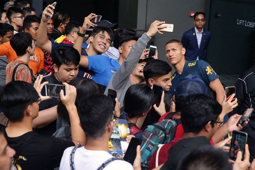 Richarlison meets fans while leaving JW Marriott Singapore South Beach for an evening training session on Oct 7, 2019.
