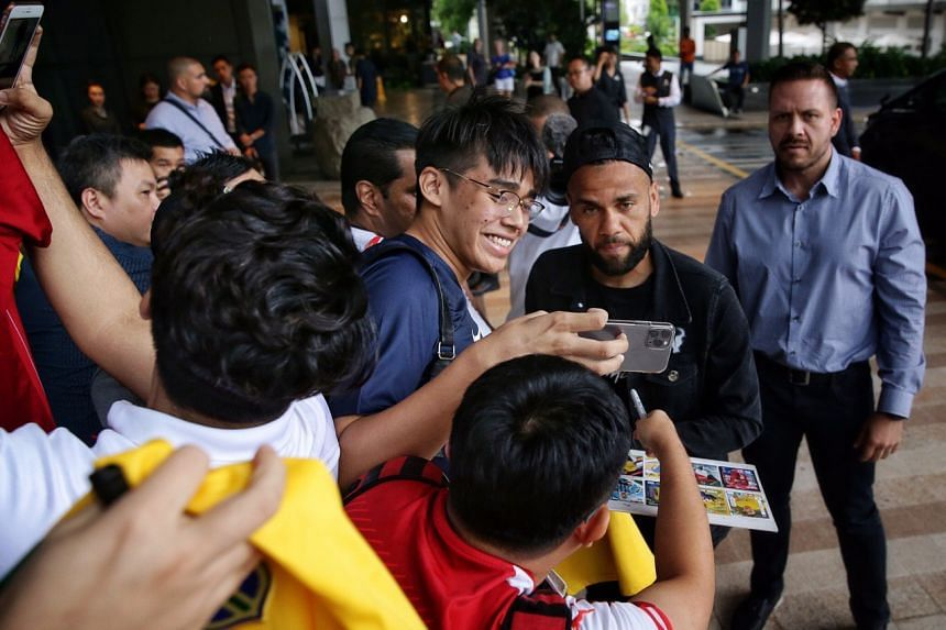 Dani Alves poses for a photo with polytechnic student Feroz Khan, 18, at JW Marriott Singapore South Beach.