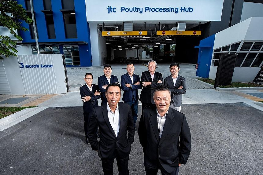 United Overseas Bank (UOB) head of group commercial banking Eric Tham (left) and Singapore Poultry Hub CEO Joseph Heng with the hub's five shareholders at JTC Poultry Processing Hub @ Buroh. UOB will be furnishing a $40 million loan for the upcoming