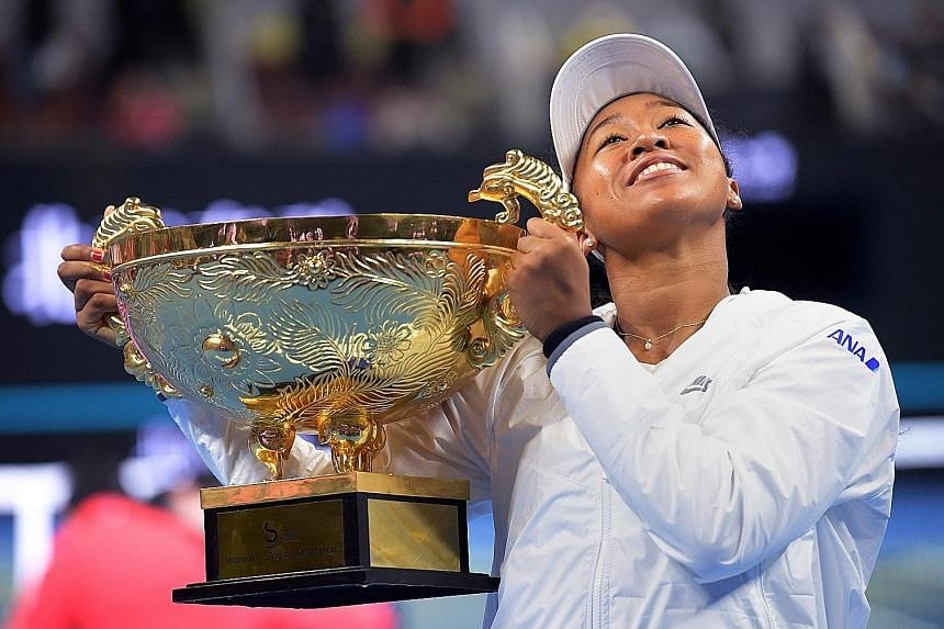Naomi Osaka hoisting the trophy from the China Open, her second straight title, having won last month's Pan Pacific Open.
