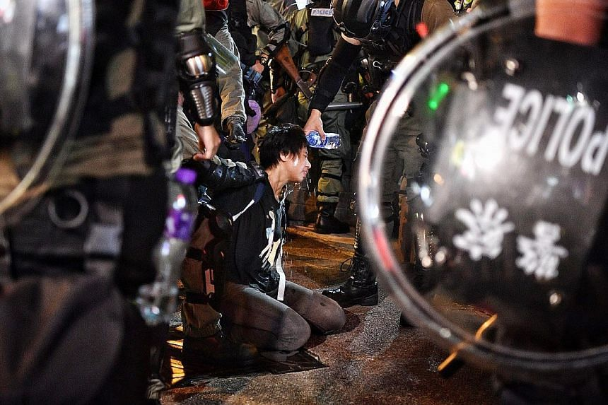 A police officer washing the eyes of a protester arrested near Prince Edward MTR station yesterday. Groups of protesters targeted several MTR stations which had been shut for the day, breaking through metal barriers and trashing the concourse. ST PHO
