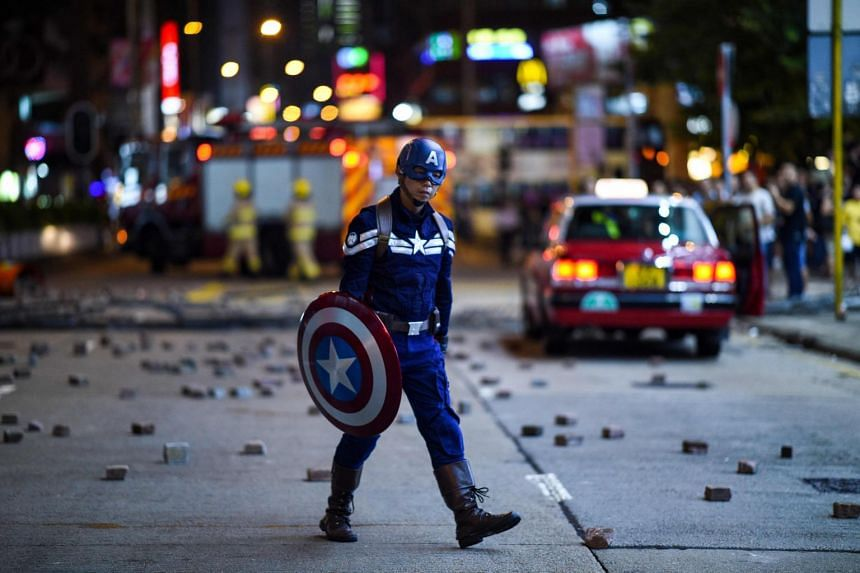 A man wearing a superhero costume walks on a street as protesters gather near the Mong Kok police station in Hong Kong on Oct 7, 2019.