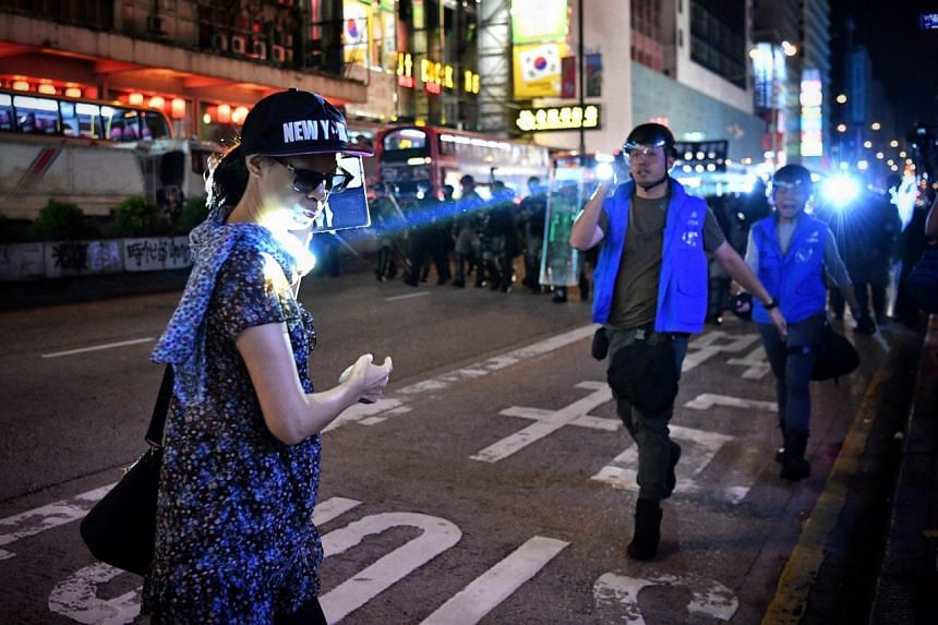 A police officer shines his torch on a woman filming the police operation in the middle of Nathan Road near Prince Edward station on Oct 7, 2019.