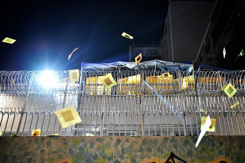 Protesters throw paper offerings in front of the police standing guard at Mong Kok Police Station on Oct 7, 2019.