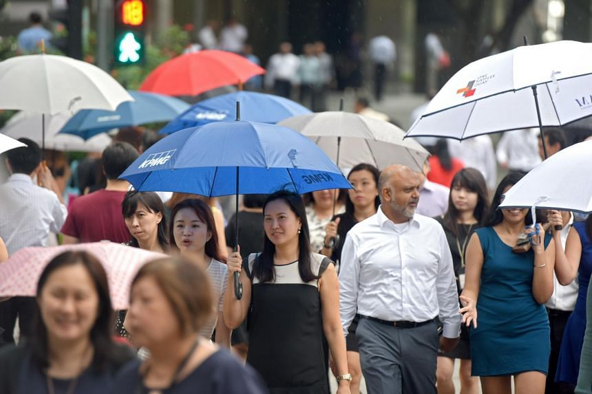 Office workers crossing the road on a rainy day.