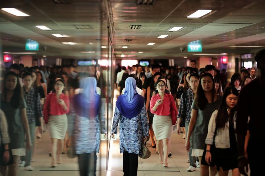 The morning crowd at Raffles Place MRT station.